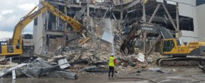 EAI performs demolition as a track-hoe knocks down building